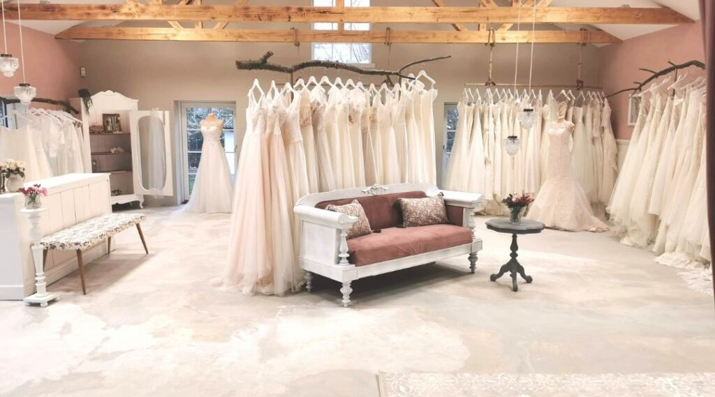 Showroom fyldt med brudekjoler og en flot, pink sofa i midten af rummet