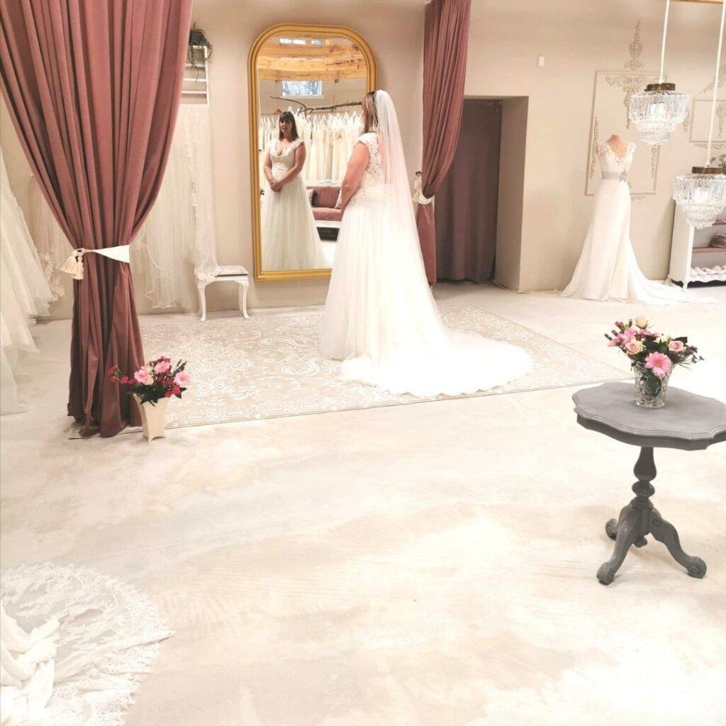 Kvinde der prøver brudekjole foran spejl i stort showroom